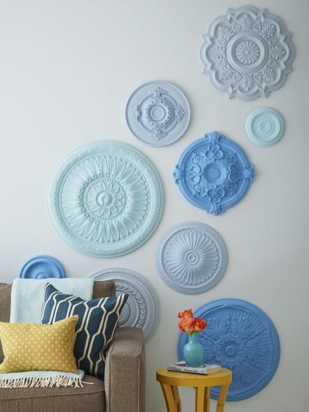 "A variety of polyurethane ceiling medallions (available at home improvement stores) make expensive-looking wall art when they're painted similar shades. The medallions are lightweight, so they're easy to hang. Use strong glue like Liquid Nails or, for a temporary hold, try strips of Velcro. Nail the back part of the Velcro to the wall to make it extra secure. ""Trace the medallions onto kraft paper. Stick the paper circles to the wall with painter's tape to help plan your design,""—Tiffany…"