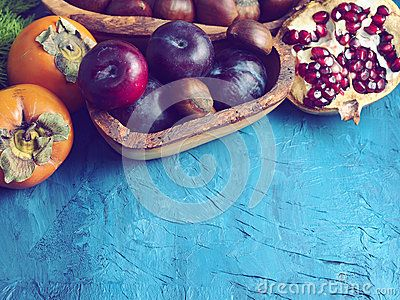Persimmons, plums, chestnuts and pomegranate on blue paper textured background with copy space. Winter still life