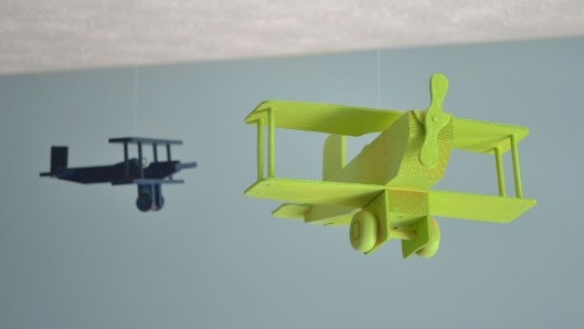 Buy inexpensive plane kits from Michaels, spray paint them, and hang them from fishing line.  Cute for a boy's room or nursery!