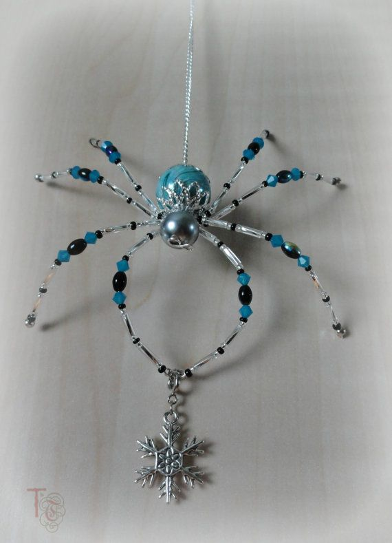 Stormy is SOLD but I have many other beautiful spiders available in my shop; Christmas Spider Legend; Spectacled Spider  Stormy is a gorgeous 4x4 inch beaded Christmas spider that shimmers and shines and cant wait to be part of your home décor. The blue and black crystals and beads are just like the blue skies that give way to dark clouds and the silver glass bugle beads on her legs shimmer brightly like flashes of lightening. She is holding a beautiful silver snowflake charm that can be…