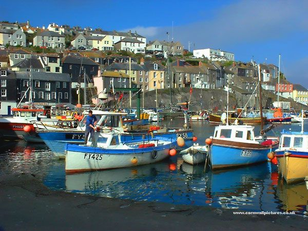 Fisherman and boats in Mevagissey harbour overlooked by Cornish cottages