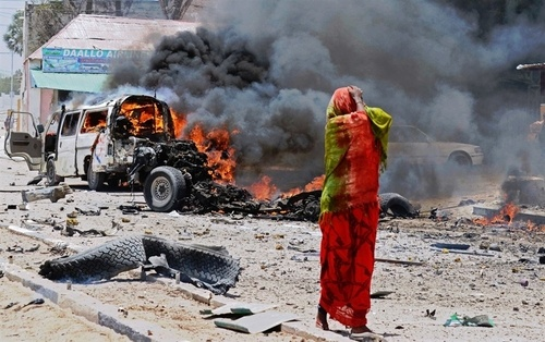 A woman reacts near the site of a car bomb in central Mogadishu on March 18, 2013. A car bomb exploded near the presidential palace in the Somali capital Mogadishu on Monday, killing at least 10 people in a blast that appeared to target senior government officials, police said.