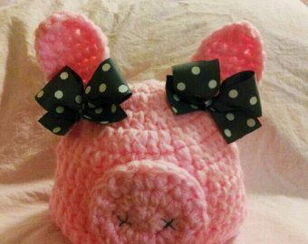 light pink crocheted piglet hat with grey and white polka dot bows. sizes range NB to adult.