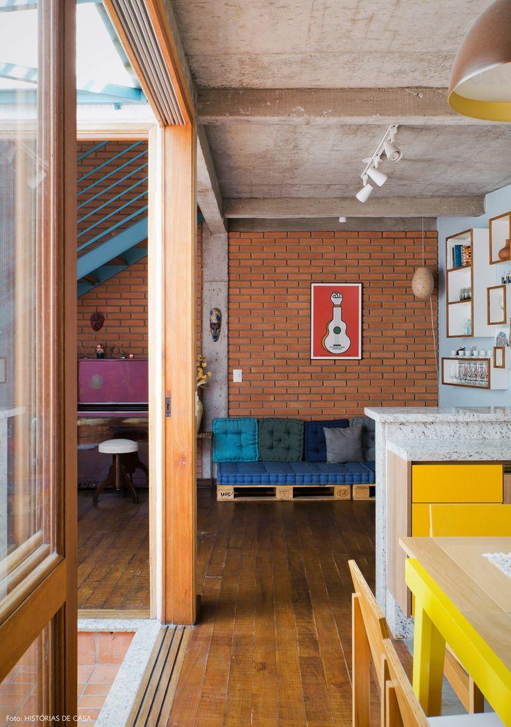 sala e cozinha integradas com parede de tijolinho, sofá feito de pallets e muitos detalhes coloridos