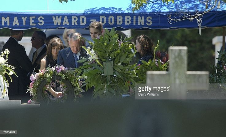 John Ramsey (2nd L) looks over the grave of his daughter JonBenet Ramsey after the graveside service of his wife Patsy Ramsey June 29, 2006 in Marietta, Georgia. Patsy Ramsey's daughter, JonBenet Ramsey, 6, was murdered under mysterious circumstances in the Ramsey's Boulder, Colorado house in December 1996. Patsy Ramsey died of ovarian cancer.