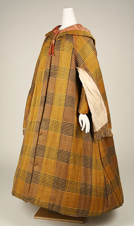 Side front view of plaid silk and cotton cloak, American, mid 19th c. Components are cloak with sleeves, cape, hood. Linings are silk and cotton. Braid trim from shoulder to opening for arm, fringed trim on edge of cape, chenille tassels on hood. MET
