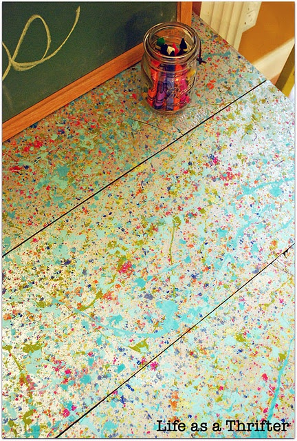 The table in my kids' playroom is getting trashed - this is a great answer for a redo - splatter art!
