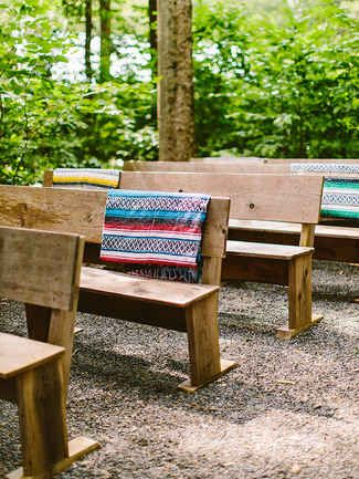 Use wooden benches or hay bails for the perfect ceremony seating at any rustic camp-inspired wedding.