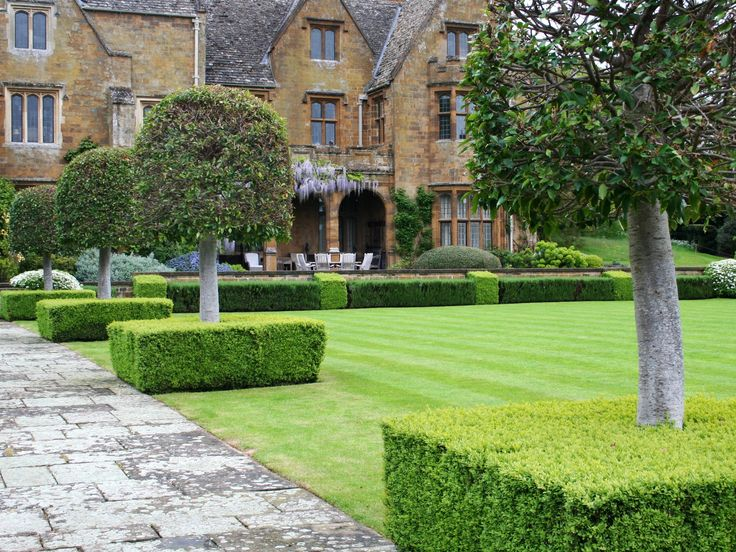 Clipped evergreen structure (Buxus cubes and Laures nobilis standards) creates the backbone of a formal design in Barton Abbey Garden
