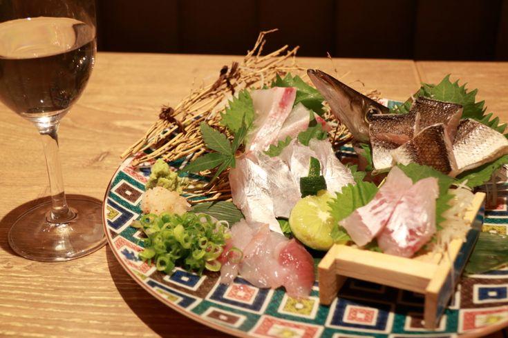 熟成肉の次はコレ! 話題の熟成魚、大阪梅田に登場 熟成肉はブームを超えて定着してきましたが、今、新たに注目を集めているのが、熟成魚です。 神戸三宮に昨年2月にオープンするなり、熟成魚と鮮魚がウマイと評判になった「神戸地魚食堂 鯛之鯛」。人気を受けて、今年5月17日に大阪・梅田にさっそく登場しました。 今回ご紹介する「地魚食堂~熟成魚と明石昼網~鯛之鯛 梅田店」です。 場所は、各線梅田駅から東へ。 飲食店密集エリア、東通商店街のアーケードを抜けてすぐ。深夜まで賑やかなエリアです。 店頭に飾られた漁網やこも樽が目印です。 階段を下りて、入り口を入ると……。 入り口を入って右手には生け簀あり。 店内…
