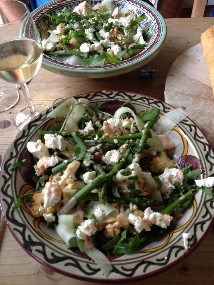 Salade met bruine rijst, amandelen, munt, harissadressing, rucola en gegrilde bloemkool