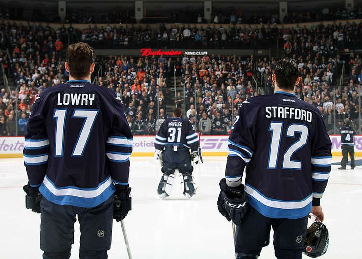 Nov.7 2015 - Flyers 3 - Wpg 0 - Adam Lowry #17, goaltender Ondrej Pavelec #31 and Drew Stafford #12 of the Winnipeg Jets stand on the ice during the singing of the National anthems prior to puck drop against the Philadelphia Flyers at the MTS Centre on November 7, 2015 in Winnipeg, Manitoba, Canada. (Photo by Jonathan Kozub/NHLI via Getty Images)
