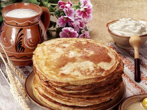 Обои Русская кухня. Огромная стопка блинов, рядом молоко, яйца, сметана, стол украшен цветами