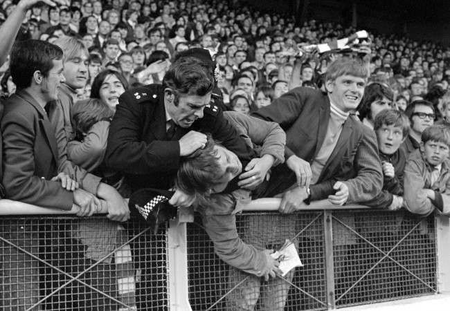 Soccer - League Division One - Manchester United v Arsenal - Anfield, Liverpool A policeman applies a headlock as he struggles with a youth in the crowd at Anfield, after hundreds of youngsters had run wild on the pitch just before the start of the First Division match between Manchester United and Arsenal. Manchester United were banned from playing at home for the first two games of the season following hooliganism at Old Trafford the previous season. Ref #: PA.1997122 Date: 20/08/1971