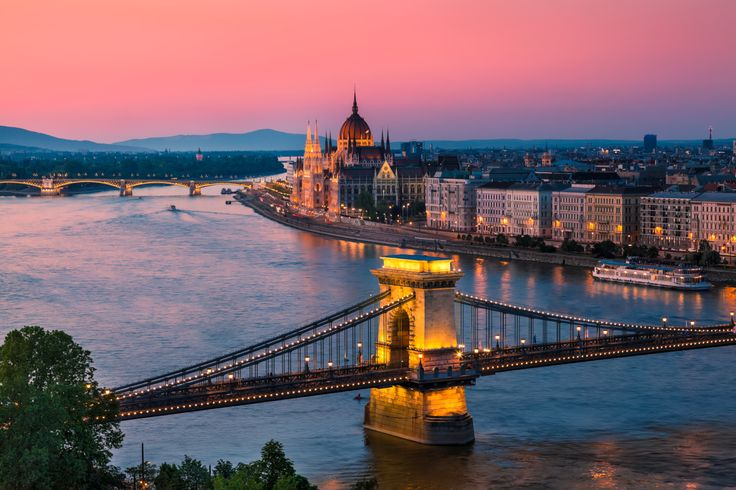 The Parliament Building and Chain Bridge glow in the finals rays of day in Budapest, Hungary.