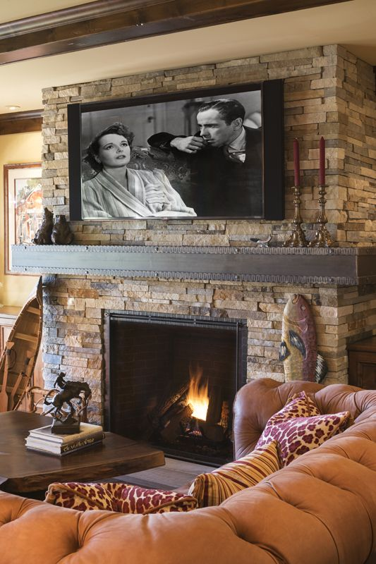 Neutral stacked stone and custom wrapped bronze mantle add richness and warmth to this basement entertainment center featuring Heat & Glo's TRUE d…