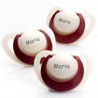 Chupetas NUK Genius em látex. Pack composto por 3 chupetas com anel vermelho. Veja a disponibilidade dos tamanhos na loja www.chupetascomnome.com