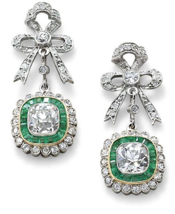 A pair of diamond and emerald ear pendants The brilliant-cut diamond bow surmount suspending a centrally-set cushion-cut diamond with a millegrain-set calibre-cut emerald and old brilliant-cut diamond cluster, diamonds approximately 2.00 carats total, length 2.5 cm
