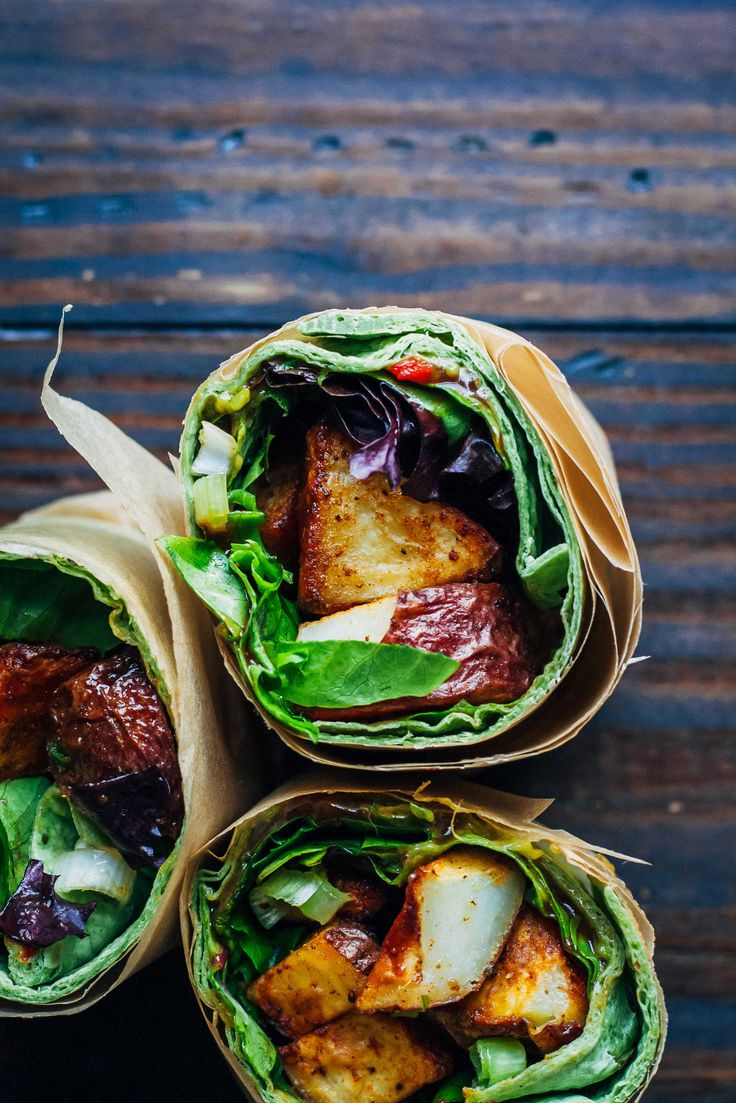 vegan wrap, made with roasted potatoes, barbecue sauce, guacamole, greens, and scallions