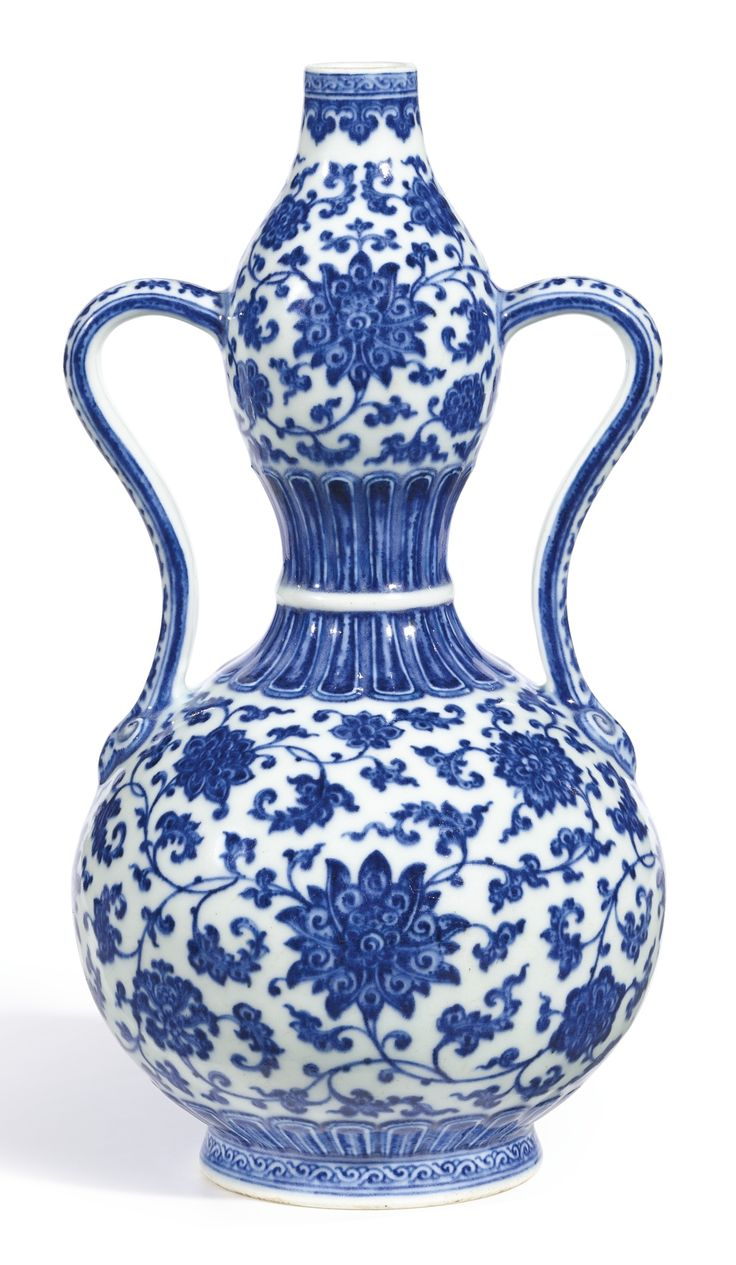 EXTREMELY FINE AND RARE BLUE AND WHITE DOUBLE-GOURD VASE, SEAL MARK AND PERIOD OF QIANLONG, flanked by elegantly shaped 'S'-handles ending in ruyi-heads, the bulbs densely painted in vivid tones of cobalt blue with meandering scrolls of stylised lotus, the recessed base centred with a six-character seal mark 29.5 cm