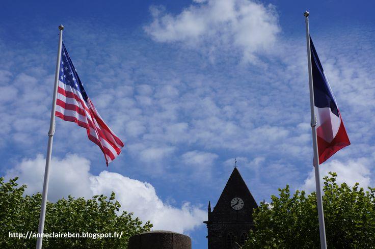 Le clocher de Sainte-Mère Eglise du haut duquel John Steele était resté accroché. American and french flags.