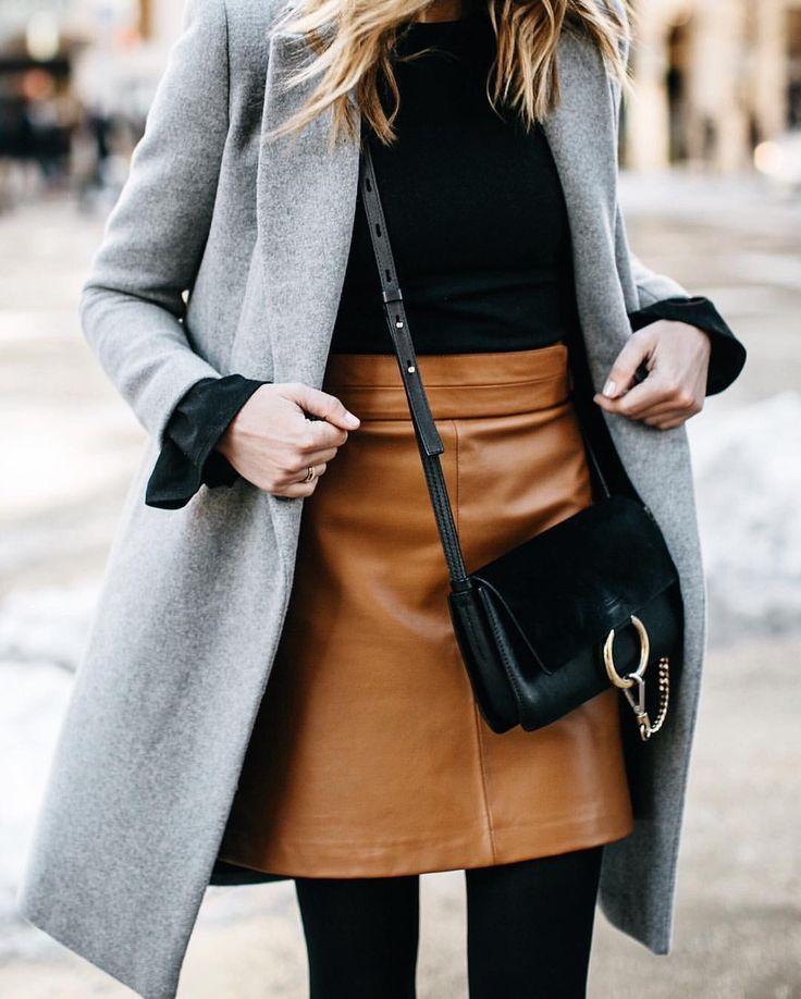 Schwarze Bluse mit braunem Lederrock und grauem Mantel mit
