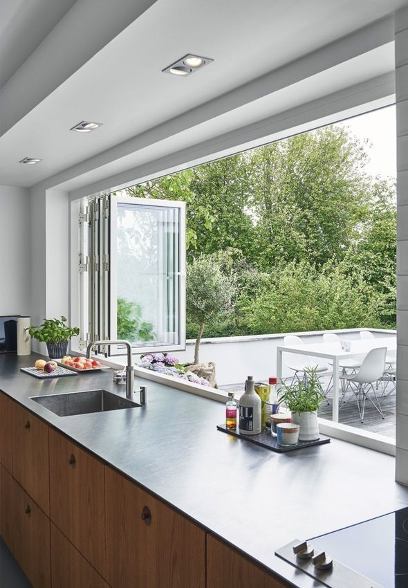 The kitchen and terrace merge with these large windows. All fronts and furniture are made in smoked oak. The kitchen tabletop made in steel with an integrated sink.
