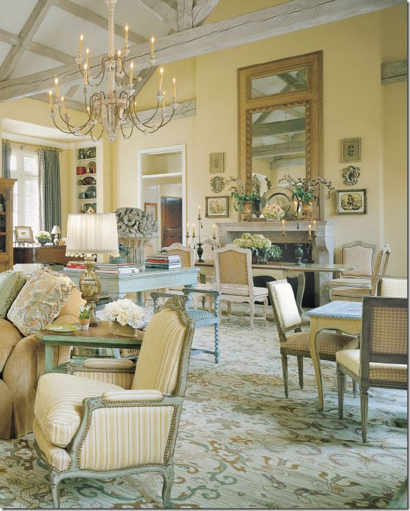 Charles Faudree at his personal best – a room filled with French antiques mostly covered in cotton checks and stripes which help to relax the priceless furniture. An extra large Italian wooden chandelier hangs low over a huge living room/dining room. The fixture is large enough that it doesn't get lost in this sized room – proportion is always something to consider.