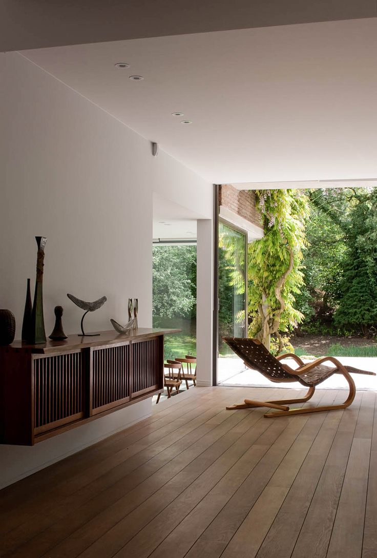 House D by architects Claire Bataille and Paul Ibens, Brussels, Belgium. Wall cabinet by George Nakashima (c.1960s) and a lounge chair model no.39 by Alvar Aalto (1937). Photograph by Jean-Luc Laloux. / Laloux