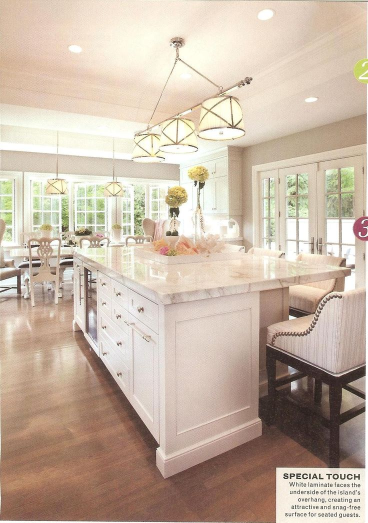 gorgeous kitchen features tray ceiling accented with grosvenor linear triple pendant illuminating large center island fitted with glass front wine cooler center island lighting