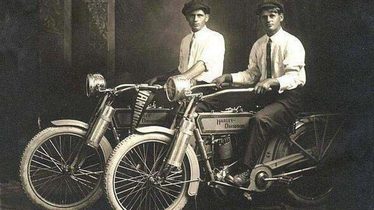 William Harley and Arthur Davidson posing with their motorcycles in 1914.