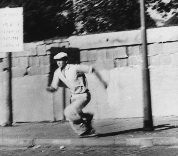 A refugee from the German Democratic Republic (DDR) is seen during his attempt to escape from the East German part of Berlin to West Berlin by climbing over the Berlin Wall on October 16, 1961. - I sure hope he made it!