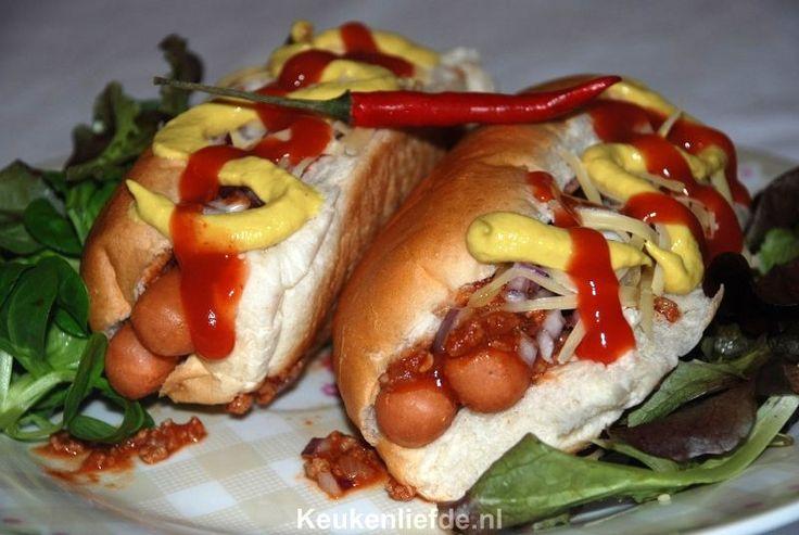 De chili dog! Een simpel broodje hotdog bedekt met een laag pittige chili en bestrooid met fijngesneden rode ui, geraspte kaas en wat mosterd en ketchup.
