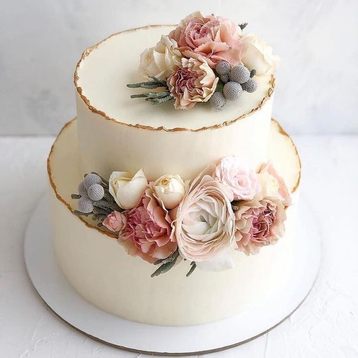 Delicate Pastel Fresh Flowers On Top Of A Simple Two Tier Cake