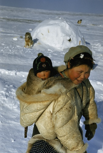 Mother carries her baby in hood of her caribou-skin parka.  Location:Near Resolute Air Station, Northwest Territories, Canada.