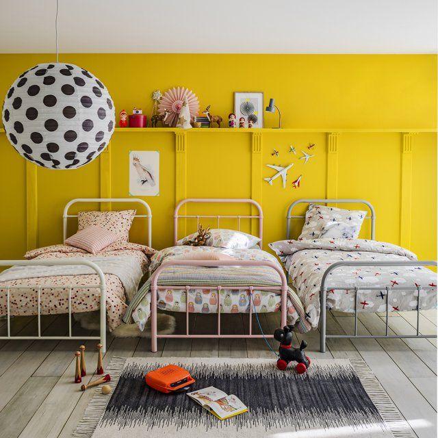 Une chambre d'enfant pour trois. Partager une chambre pour les enfants n'est pas synonyme de bazar assuré, la preuve avec ses trois lits vintage et disposés de manière parfaitement parallèle.