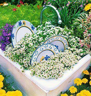 The originator of this idea took an old sink and turned it in to a lovely garden with some plates that are perhaps broken on the buried edge. The faucet works to water the little area.