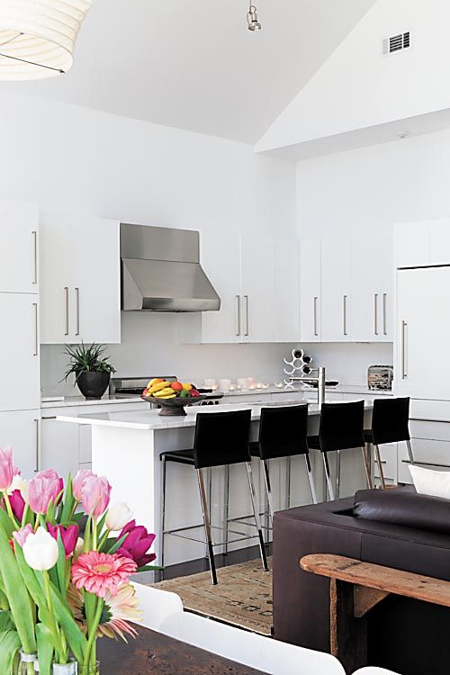 In the kitchen, meeks combined white marble counters, white cabinetry with a high-gloss lacquer finish and stainless steel. Black counter chairs provide graphic contrast. - Photo by Sara Essex