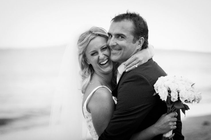 Bride and groom in playful mood after their wedding at home at Milford beach, Auckland. Black and White.  beguiling fine art family photographs for the walls of the most discerning clients homes. We specialise in wedding and family portrait photography, and supply prints on the highest quality media, framed in beautiful conservation standard frames. We are a high end studio located in the beautiful city of Auckland, New Zealand.