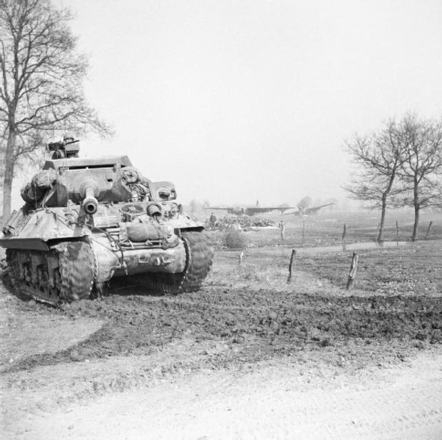 Achilles tank destroyer on the east bank of the Rhine moves up to link with airborne forces whose abandoned gliders can be seen in the background.