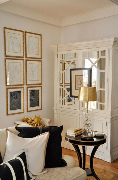 Megan Winters Elegant living room with ivory mirrored cabinet, gold leaf  frames art gallery,