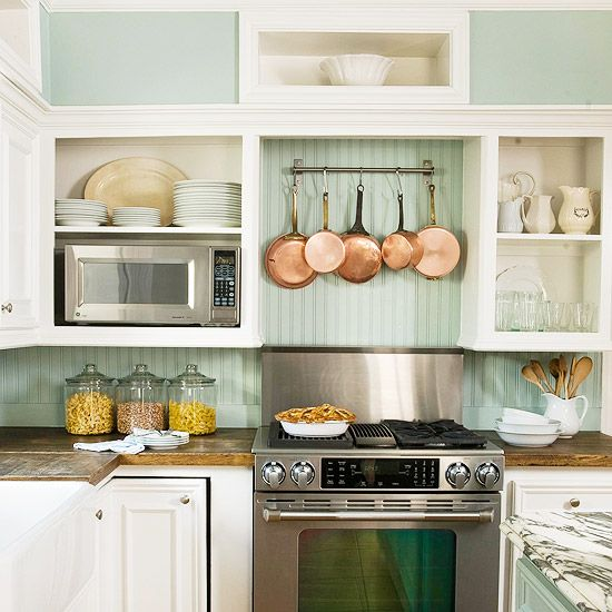 Note to self: pot rack. (Really, really cute above the range, especially if there's no hood with ventilation.)    It's the beadboard backsplash and hanging copper pans that give this kitchen a warm, cottage feel.