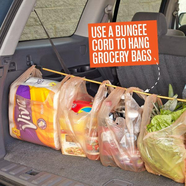 grocery bags hanging off a bungee cord in the backboot of a car,