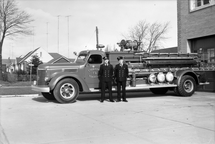 Captain William Coxhead, FMN.,  and F. MacFadden pose in front of the Etobicoke Fire Department hall at Royal York Road and Tenby St., in Humber Bay, on November 14, 1954.