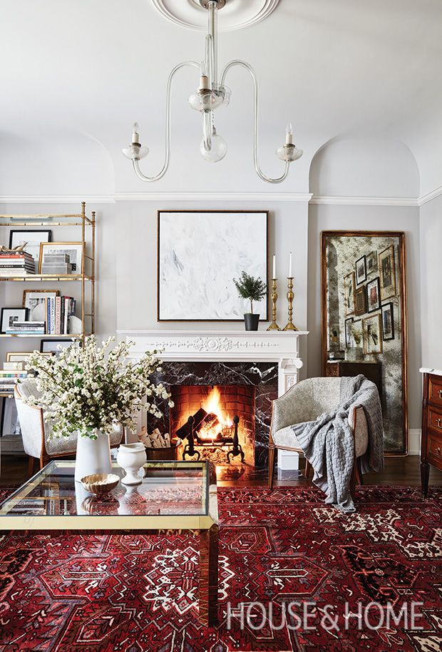 This living room is a fresh take on traditional style, with old-world classics like the mantel and Heriz rug balanced by clean-lined chairs that invite you to cozy up and relax by the fire.   Photographer: Stacey Brandford   Designer: Allison Willson
