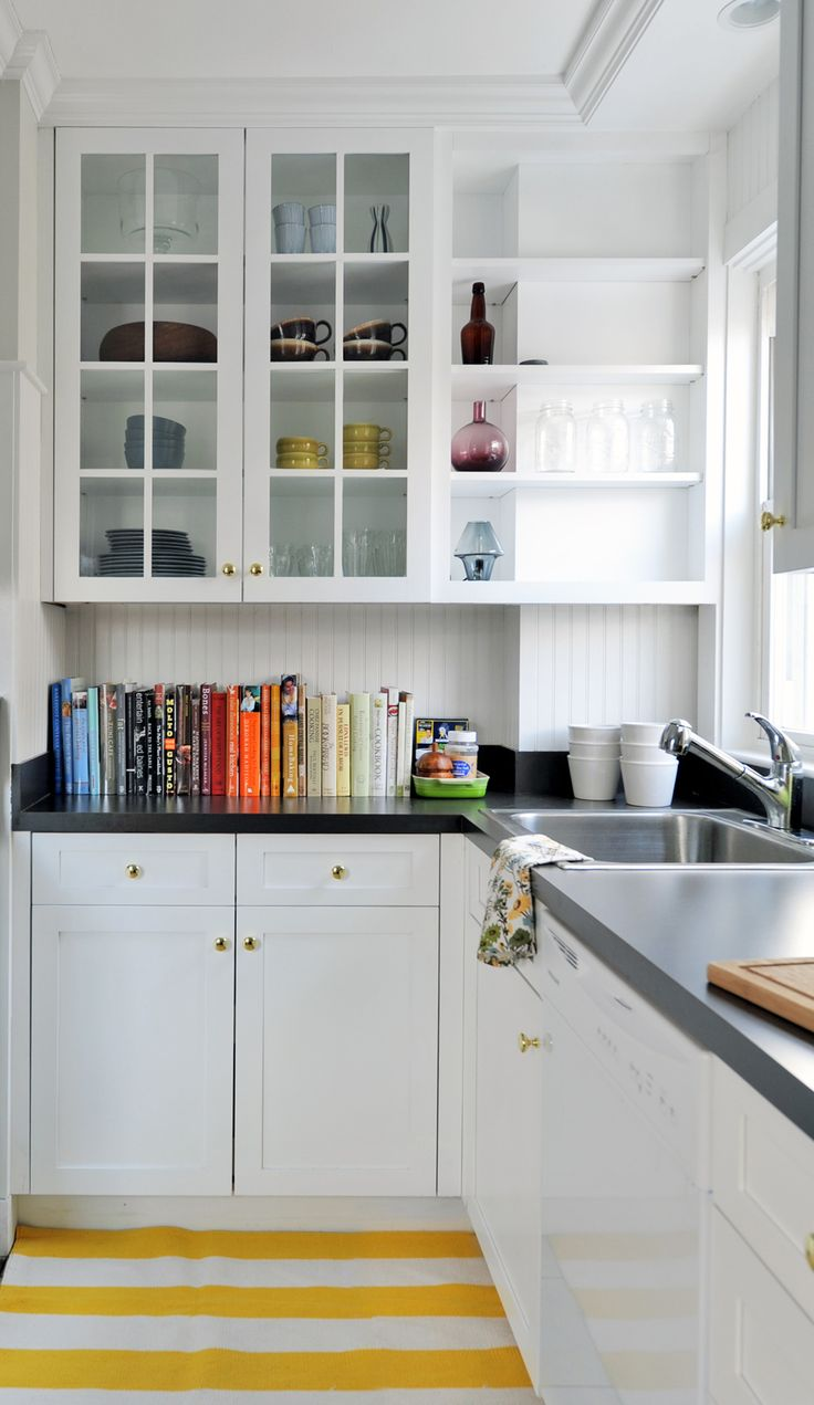 lovely + simple kitchen; white + black palette; open shelves mixed w/glass cabinets; books adding color; yellow + white cotton rug; soapstone counters