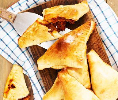 Dessa tacopiroger är en favorit för både stora och små! Pirogerna fylls med stekt nötfärs, tacokrydda, tomatsås och rivna morötter för att sedan vikas ihop, penslas med uppvispat ägg och gräddas i ugn. Servera de gyllenbruna tacopirogerna med svalkande gräddfil och krispig sallad.