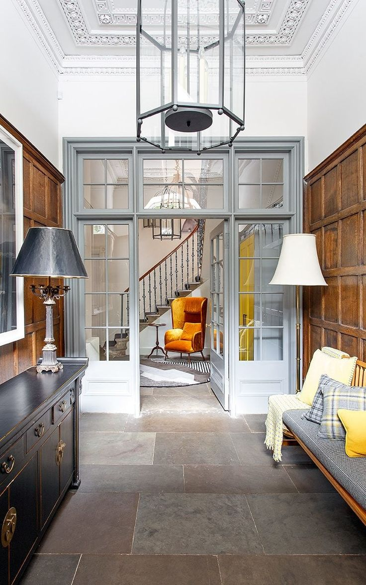 The glazed inner door in the entrance hall has been painted grey to offset the rich tones of the wooden panelling
