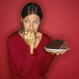 woman feeling guilty about eating chocolate cake