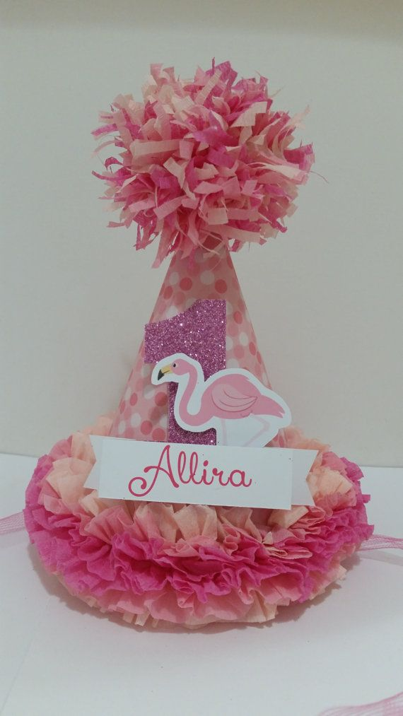 Flamingo Custom Made Party Hat You are purchasing a single custom Australian made Party Hat, In design Birthday Flamingo  Great for use at First Birthday, Photo shoots and for a cake smash.. Handmade using 200 gsm card and crepe paper Hat measures approximately 19 cm tall by 15 cm wide. Ribbon Ties (no Elastic) attached 100% Nylon Ribbon. CAN be made in other colors and numbers and can come with Elastic( please specify) Party Hat comes fully assembled ready to wear. Hat can have a named…